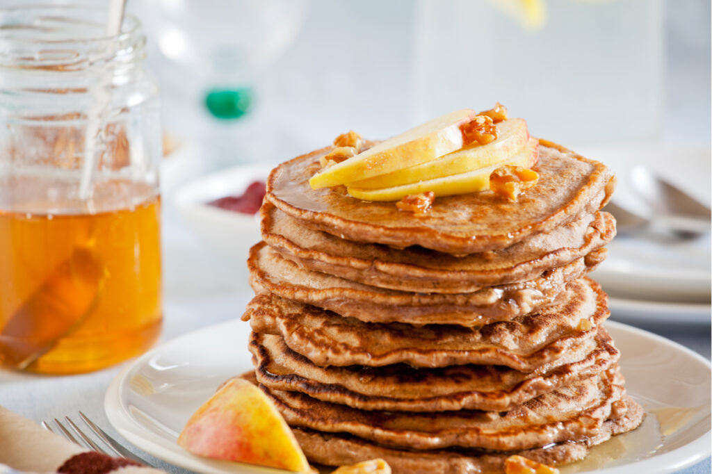 Stack of homemade whole wheat pancakes with fruits and nuts is a good holiday breakfast idea.