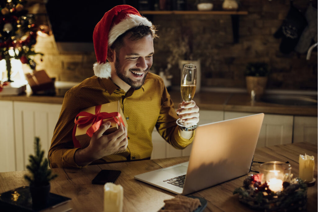 Young happy man having video call over laptop and toasting with Champagne while celebrating Christmas alone at home.
