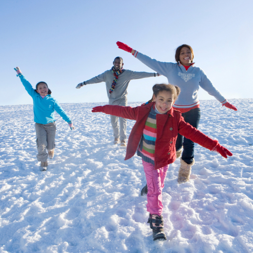 Family on winter vacation running down snowy hill smiling.