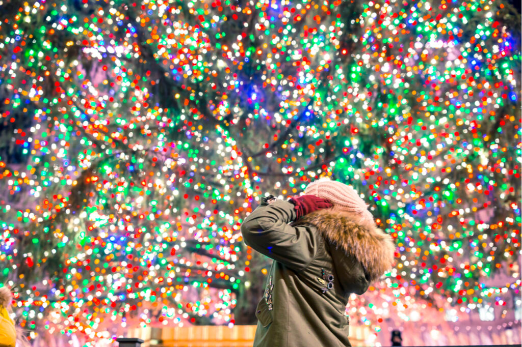 Woman happily looking at the decorated neighborhood Christmas tree.