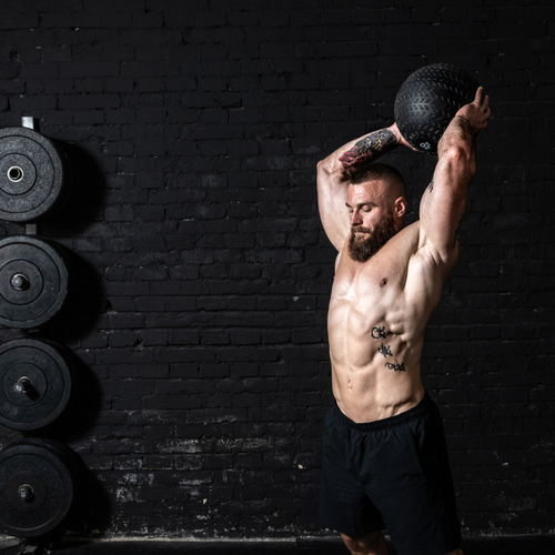 Man with big muscles doing ball throwing on the floor as hardcore cross workout training in the gym.