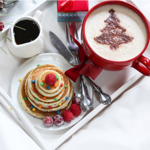 Christmas breakfast served on white tray with pancakes and cappuccino