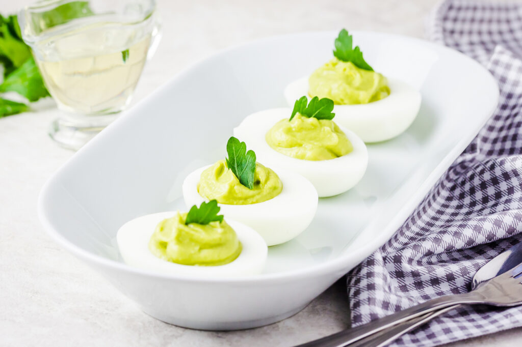 Avocado devilled eggs with parsley on white background.
