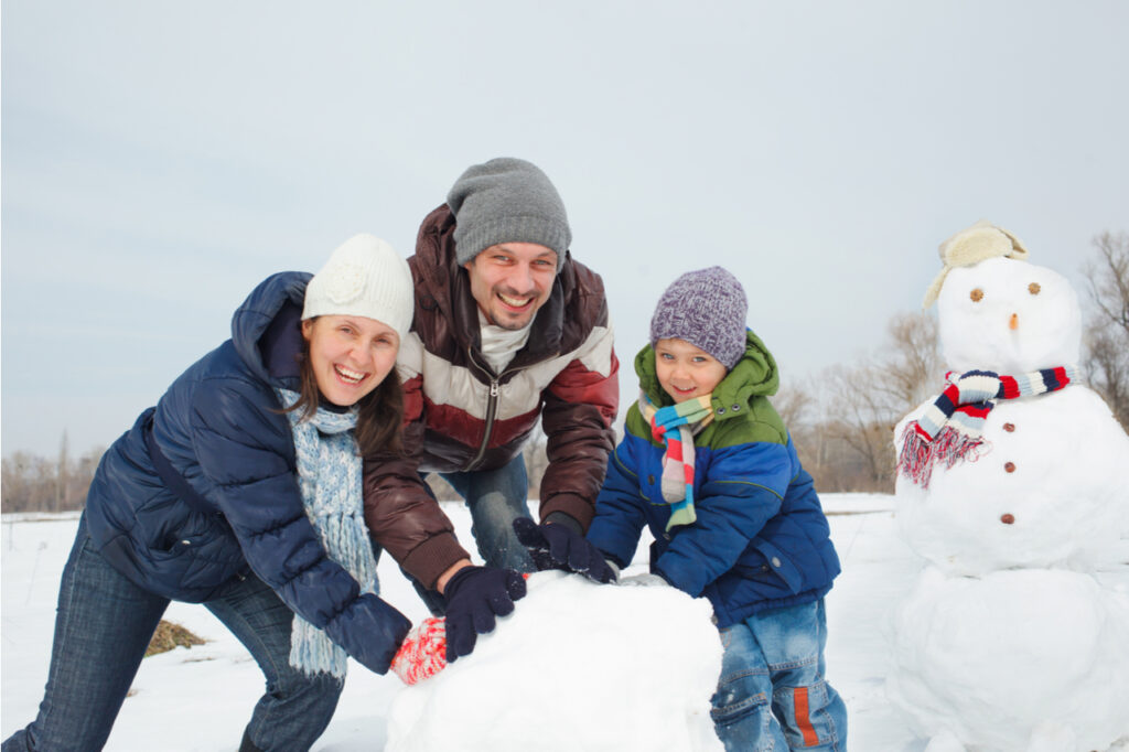 Happy beautiful family building snowman outside as part of their winter activities.