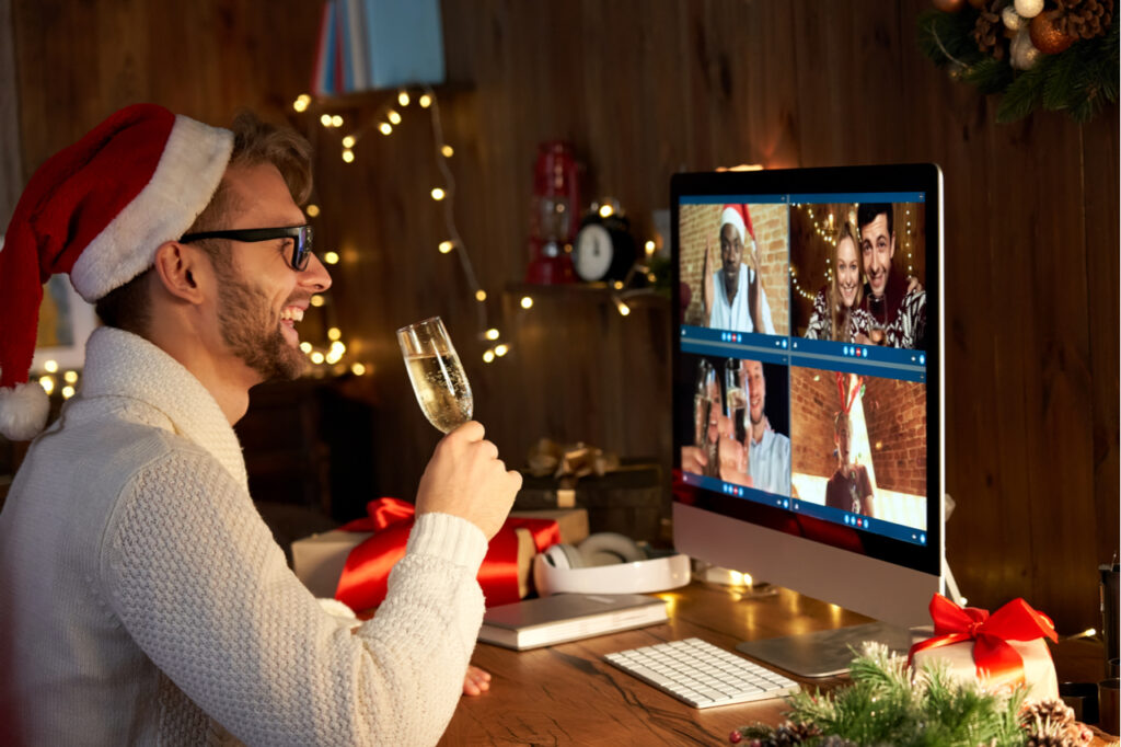 Happy young man wears santa hat drinking champagne talking meeting friends on virtual zoom video call celebrate the holiday.