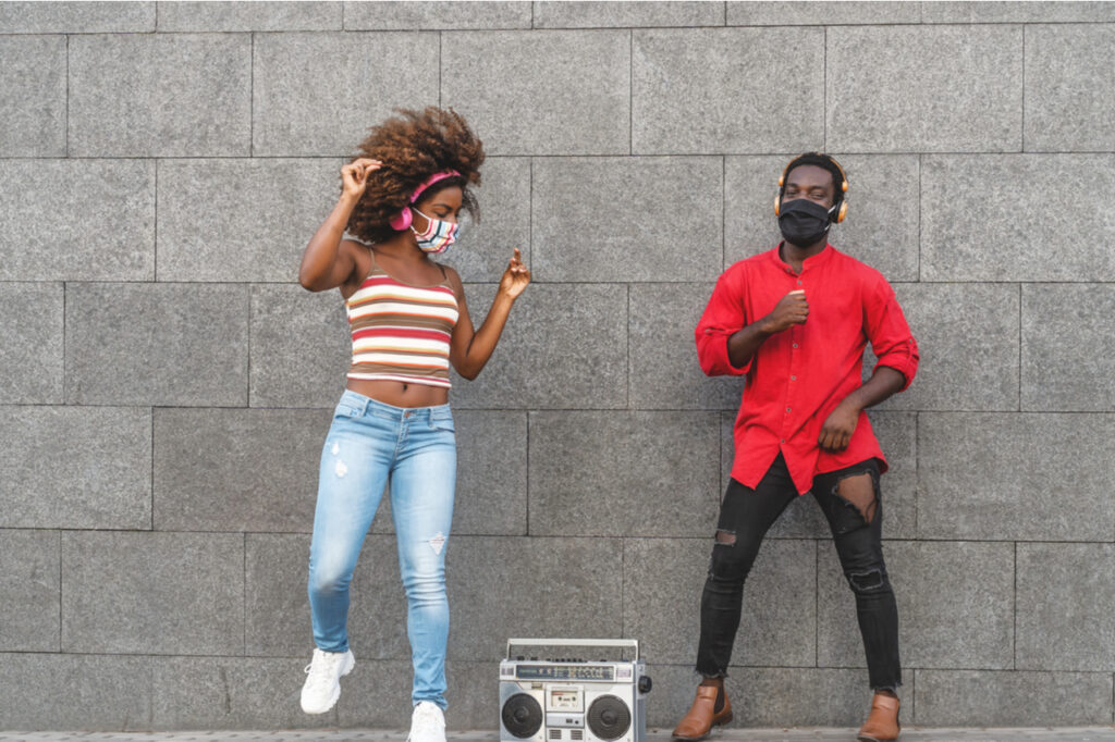 Young African people wearing face mask dancing outdoor while listening to music with wireless headphones and vintage boombox