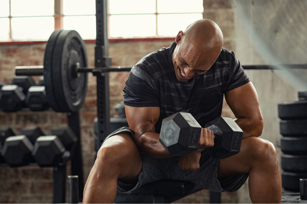 Muscular guy lifting dumbbell as a Home gym essentials while sitting on bench at gym.