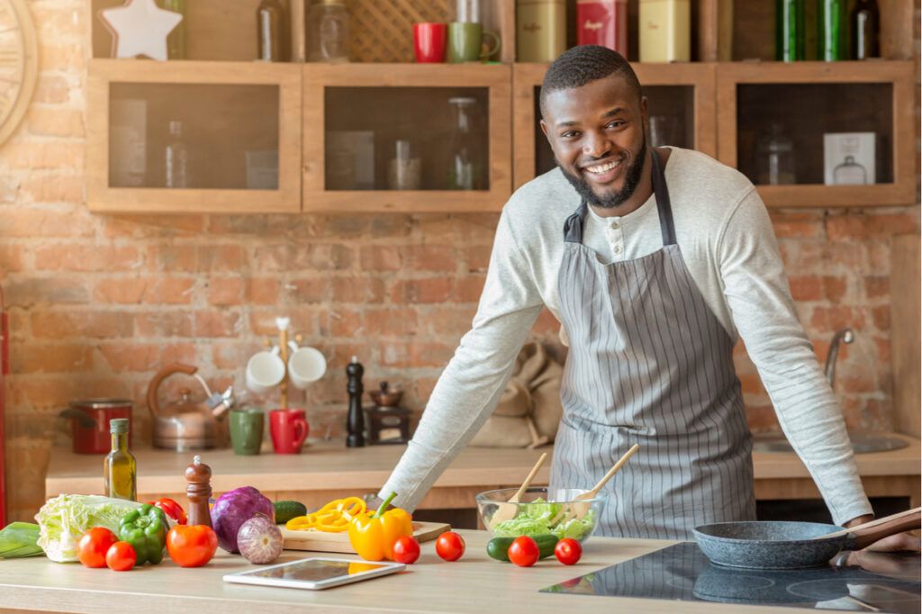 Attractive black positive man posing at kitchen while cooking dinner for his family, free space