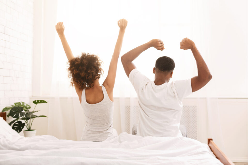 Happy black couple waking up in morning, sitting on bed, stretching in cozy bedroom, back view, free space