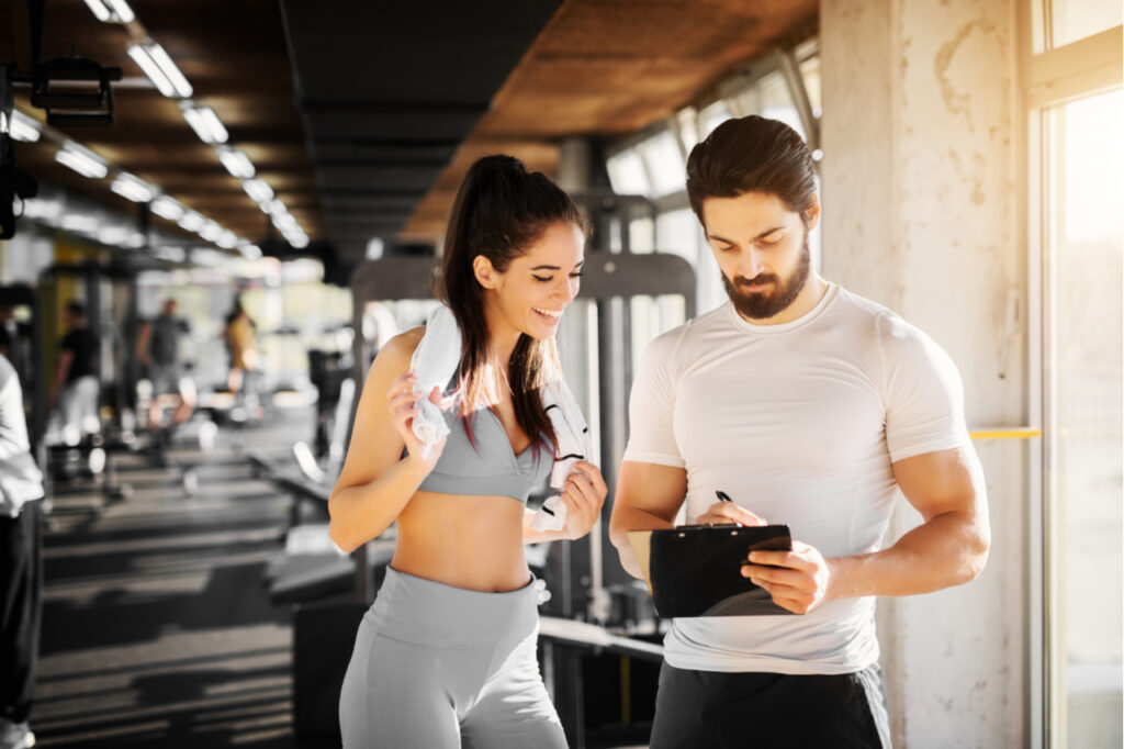 Young slim fitness girl standing with a towel near handsome trainer while showing her schedule for next week in the gym. Maintain a schedule may help improve cognitive function.