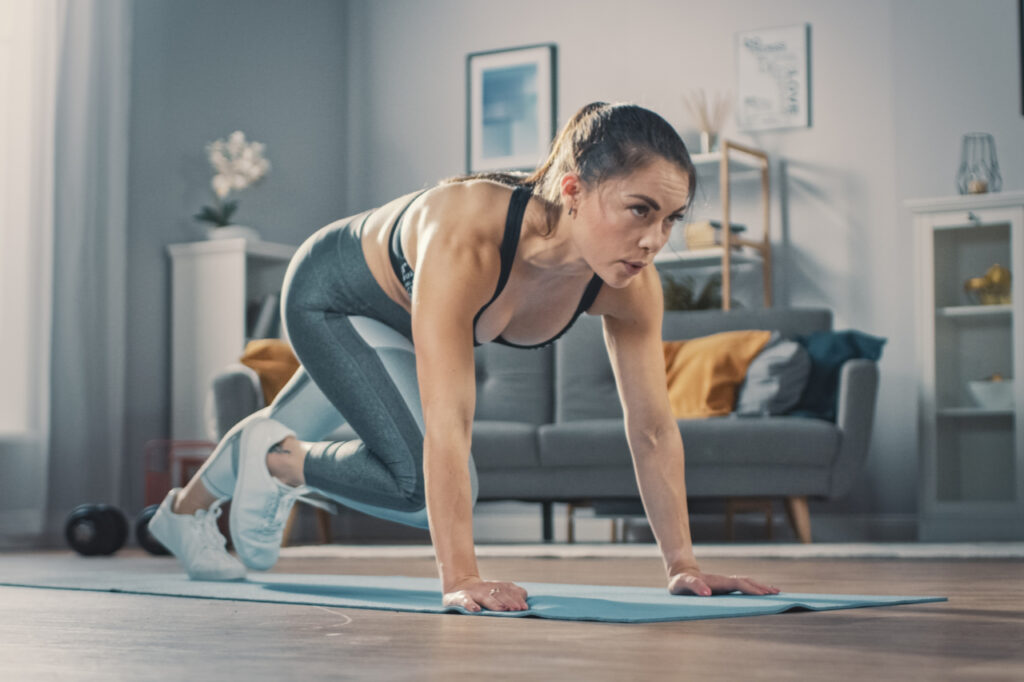 Woman doing mountain climber exercise in her living room.