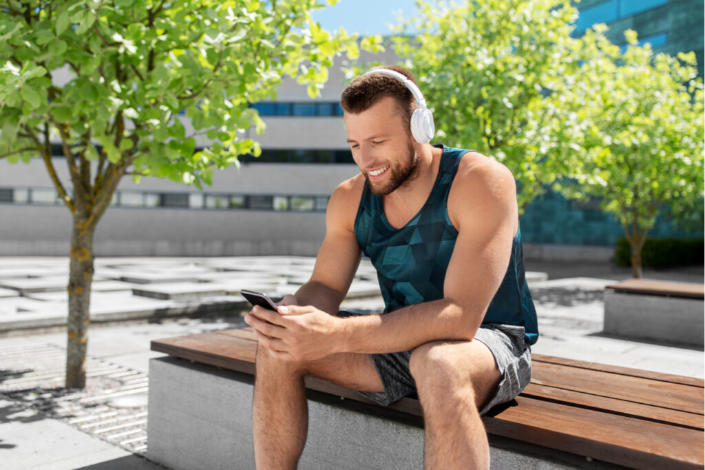 A sporty looking man listening to a podcast about fitness. Replacing negativity. Also, saying thank you to people attracts more positive energy.