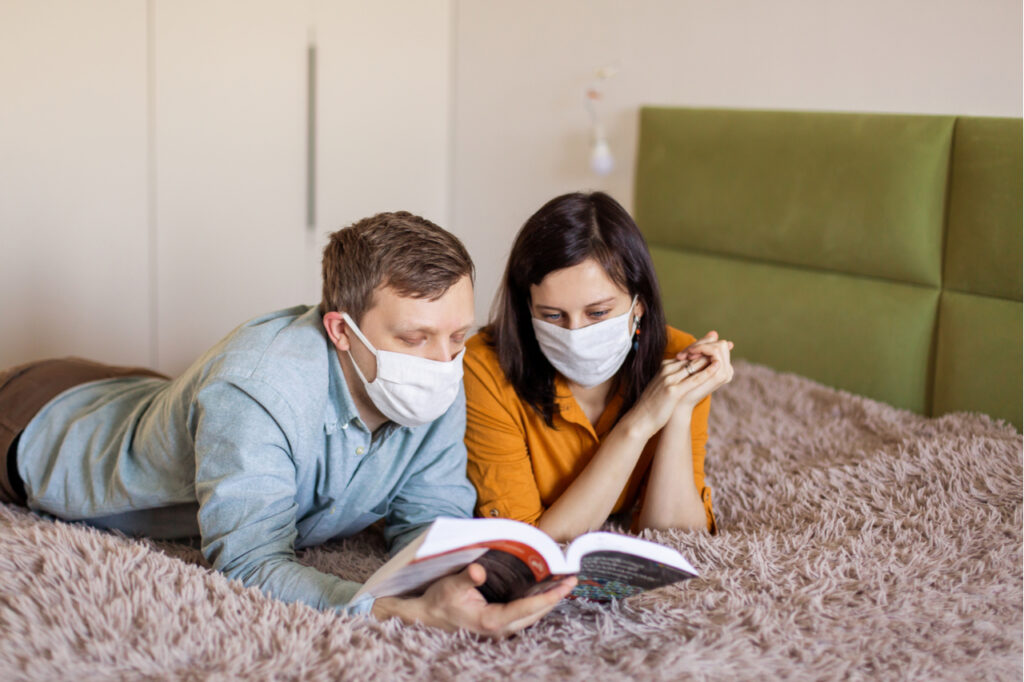A young couple is sitting at home on self-quarantine. Husband and wife quarantined coronavirus in protective masks. New reality. Normal life in isolation. Read a book together.