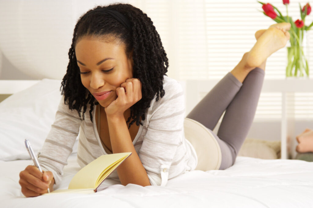Happy woman writing in her journal on the bed.