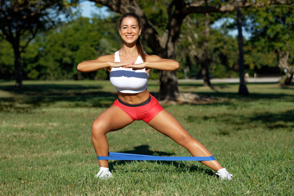 Athletic woman workout with resistance band outdoors.