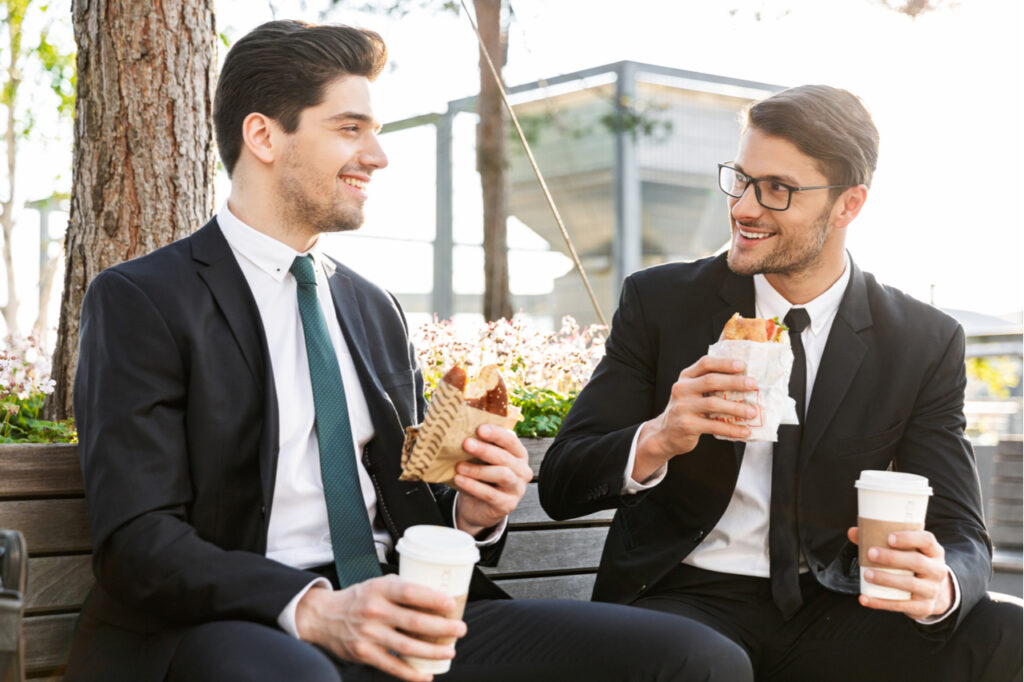 Two attractive smiling young businessmen wearing suits talking while having a lunch break outdoors at the city streets, drinking coffee