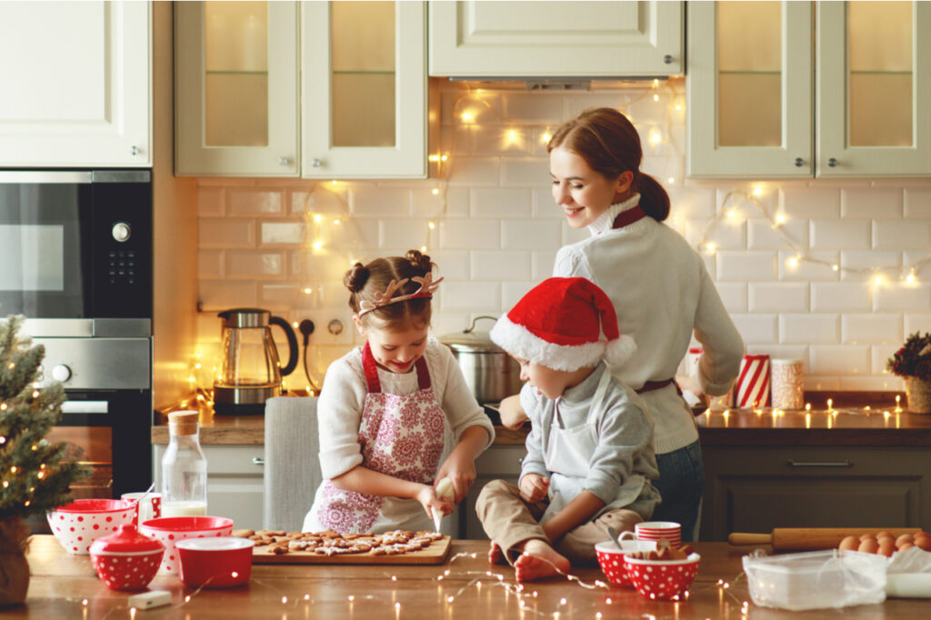 Mother and children bake christmas cookies.
