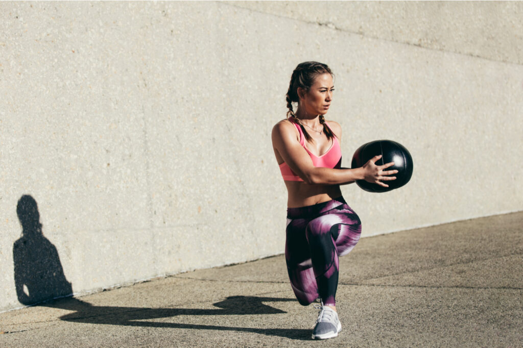 Sportswoman doing stretching exercise with medicine ball.