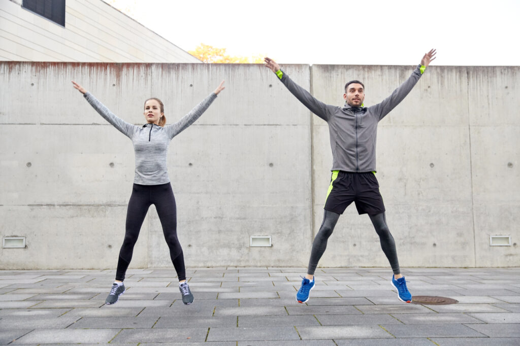 Happy man and woman doing jumping jacks for their morning exercise.