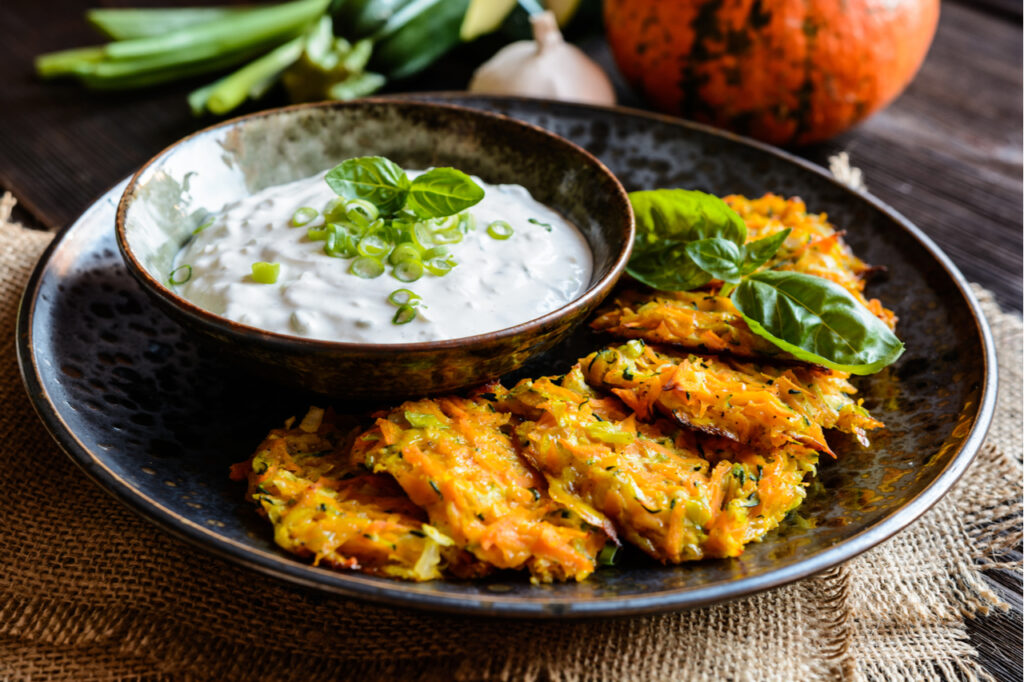 Zucchini fritters in a plate with a dip on the side.