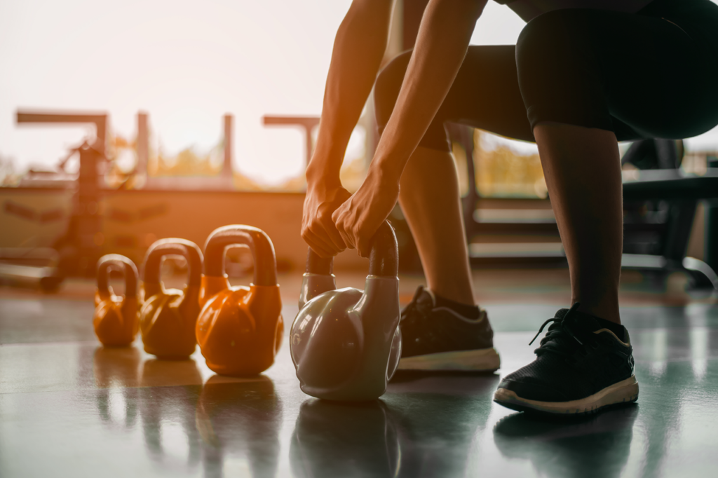 Woman in exercise gear standing in a row holding dumbbells like ybell during an exercise class at the gym.