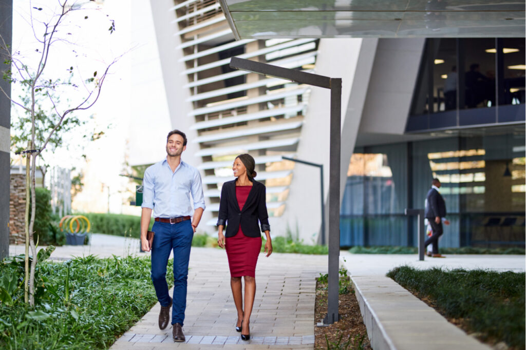 Colleagues smiling and talking while walking together on the grounds of an office complex.