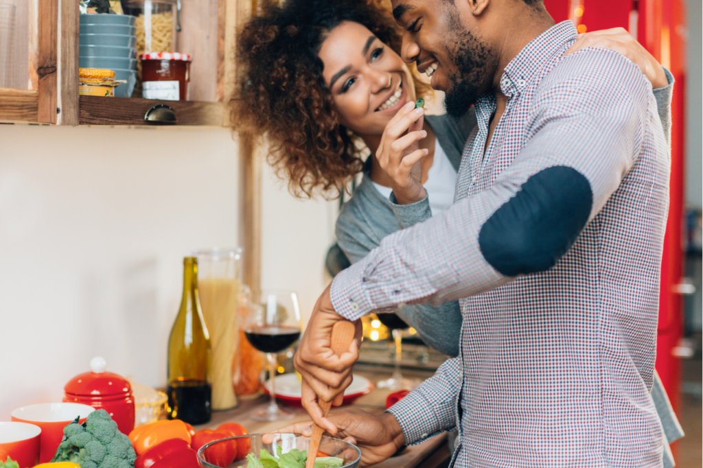 Young couple cooking playfully in the kitchen as valentine's day date ideas.