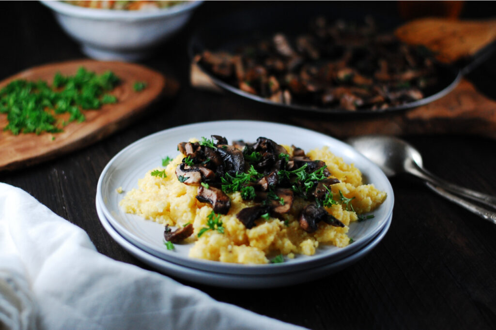 Creamy polenta with fried mushrooms and fresh herbs for lunch.