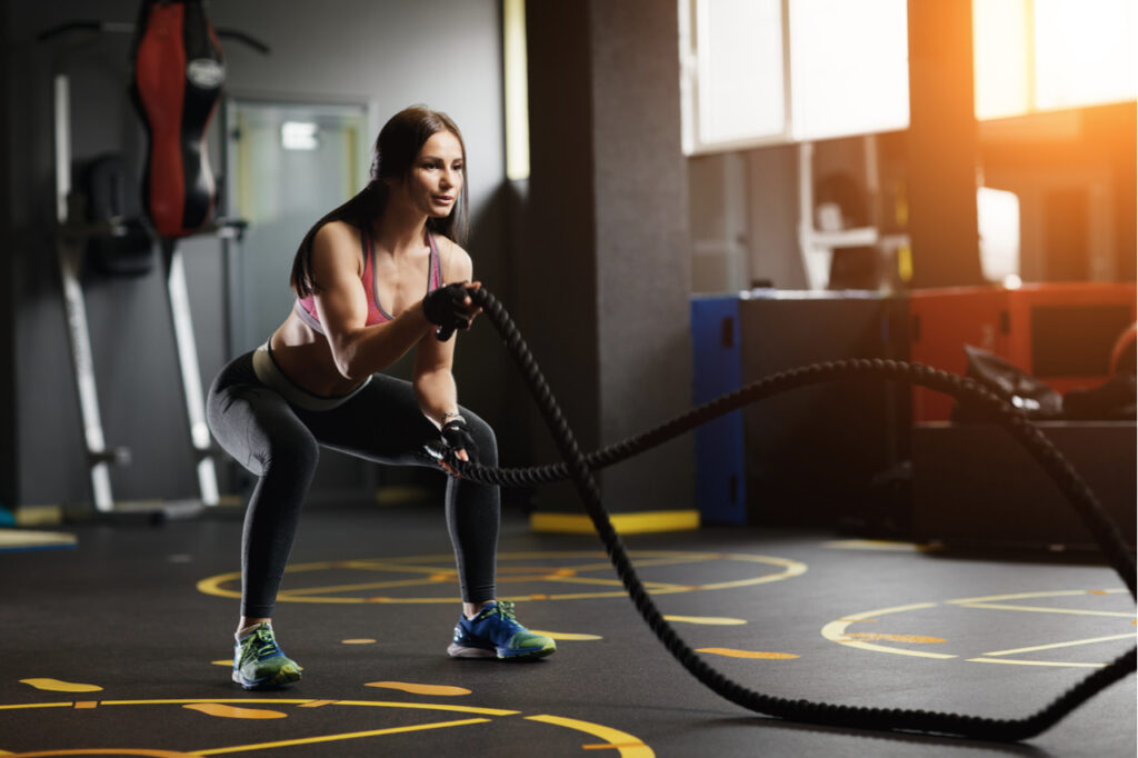 Athletic young woman doing crossfit exercises with a rope.