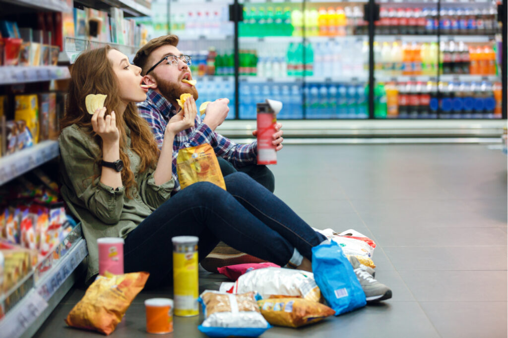 Young couple eating junk foods in a grocery isle. Avoid junk foods for cancer prevention.