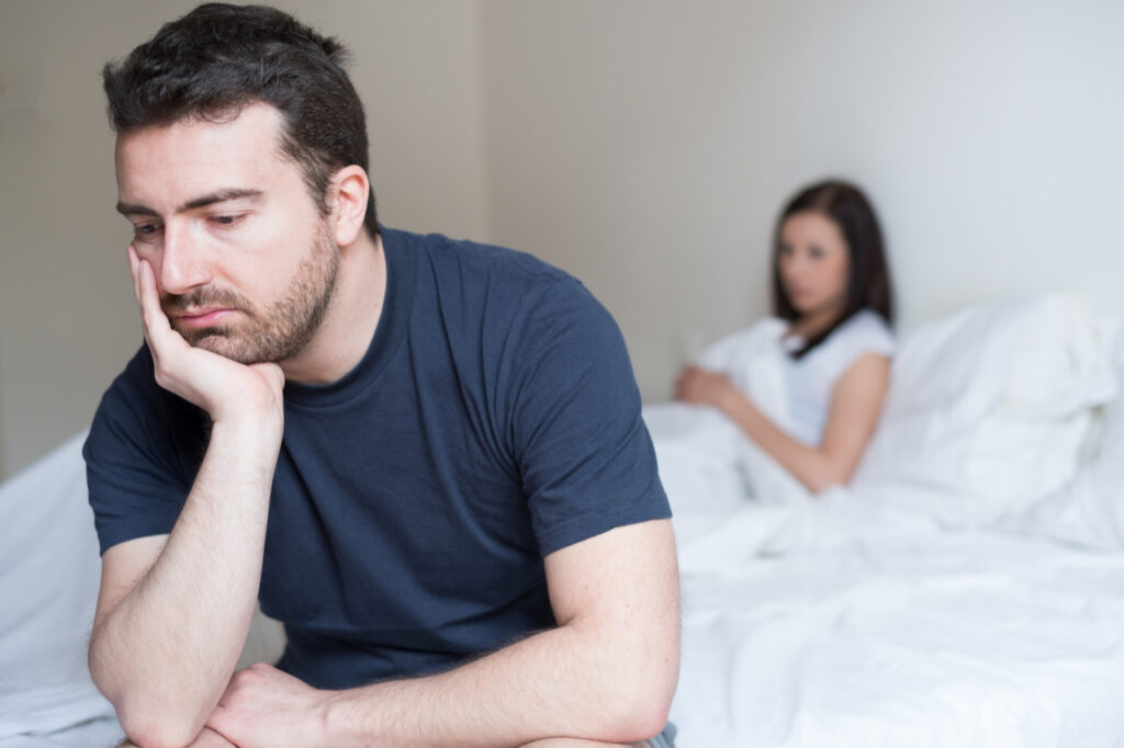 sad looking man sitting on the edge of the bed looking disappointed.