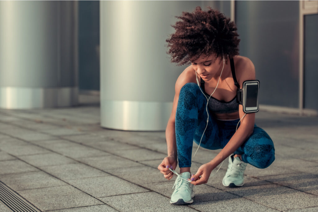 Woman in sportswear and earphones is lacing running shoes during morning run.