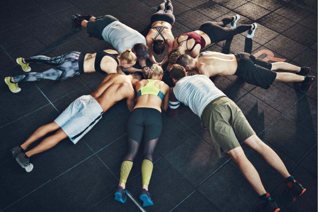 Fit young people focused on planking in a circle in a gym.