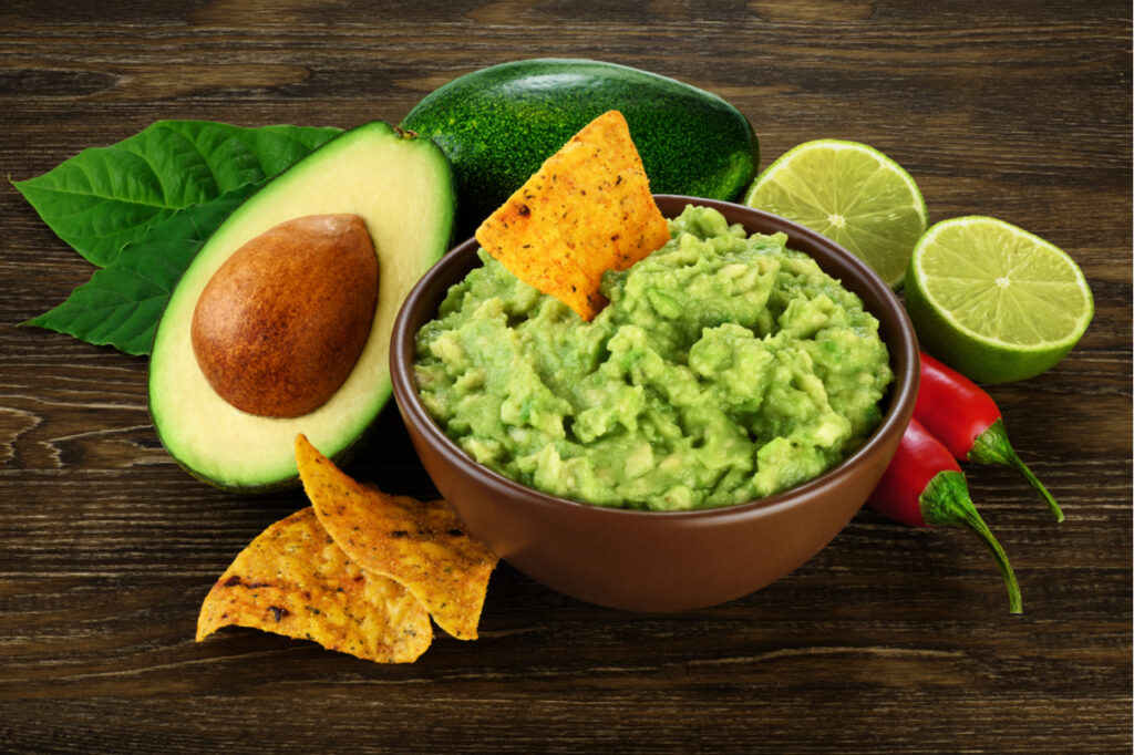 Guacamole in a bowl and nachos on the side, avocado sliced in half, sliced lime and 2 chilis.