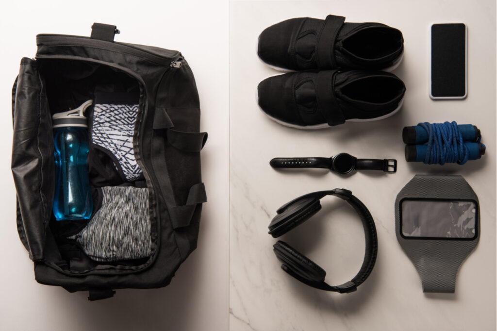 Flat lay with sports bag and arranged sports equipment on white and marble.