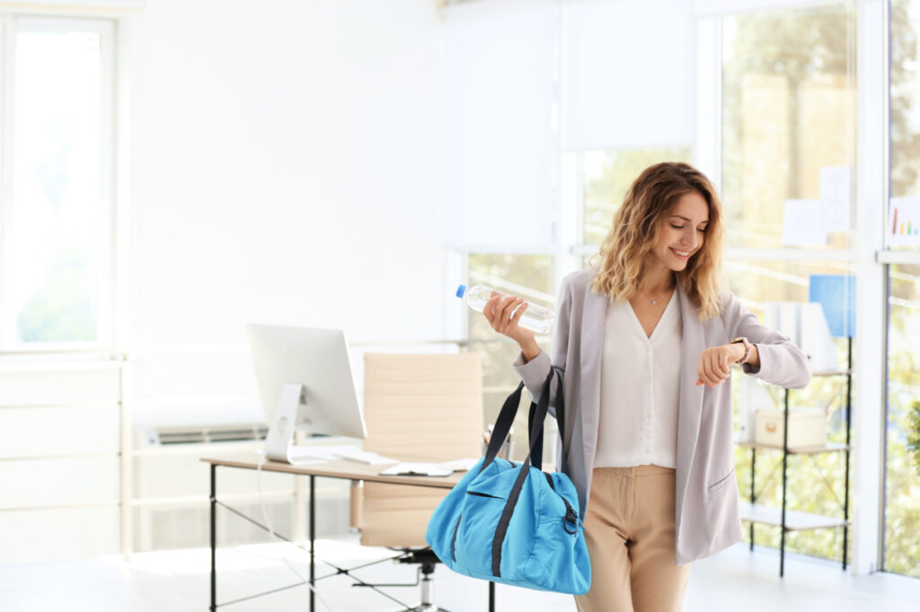 Young beautiful businesswoman holding fitness bag in office.
