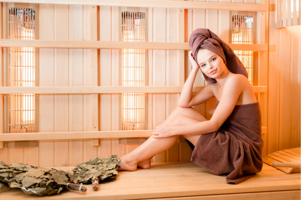 Young woman relaxing in a sauna dressed in a towel. What wellness trends are you willing to try?