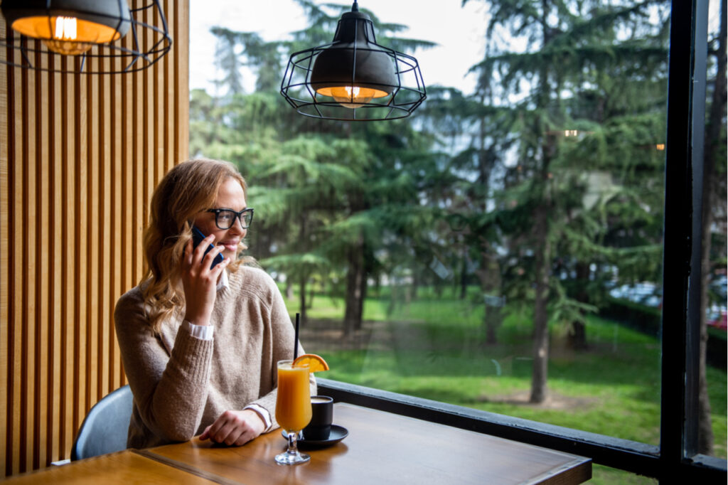 Young charming woman calling with cell telephone while sitting alone in coffee shop during free time.