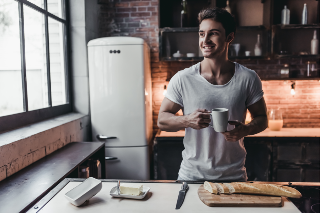 Handsome man on kitchen is smiling and drinking coffee in the morning.