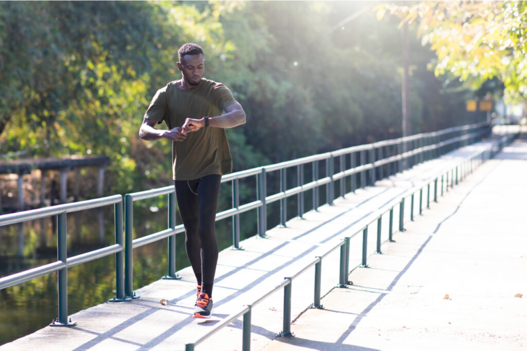 Black Man jogging and running beside road in park at autumn morning