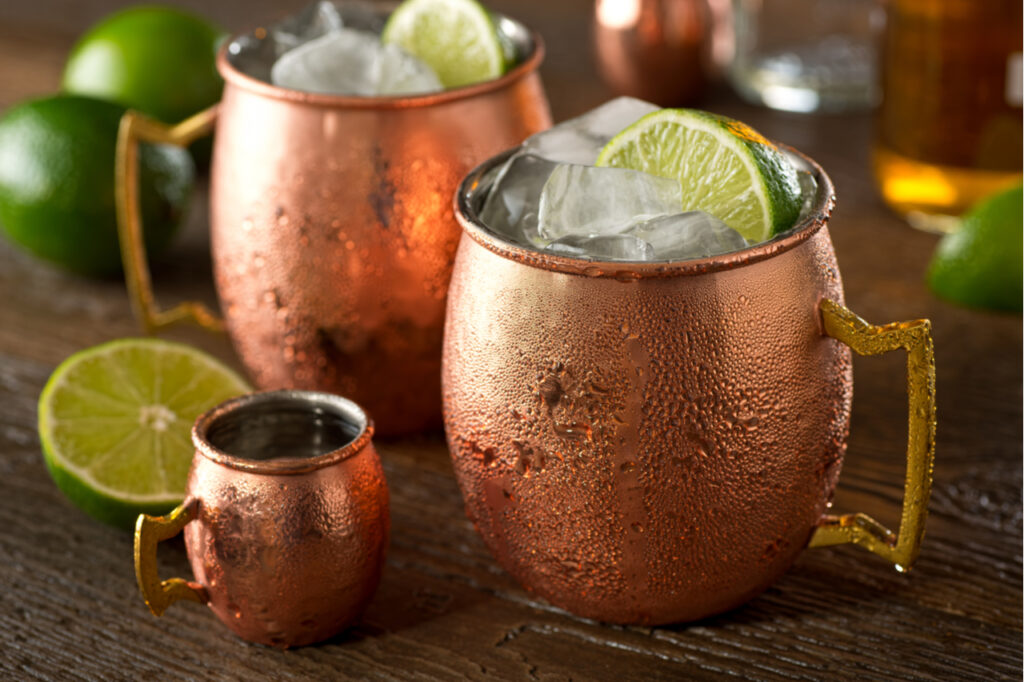 Moscow mules in 2 copper mugs with sliced lime, the best winter cocktail.