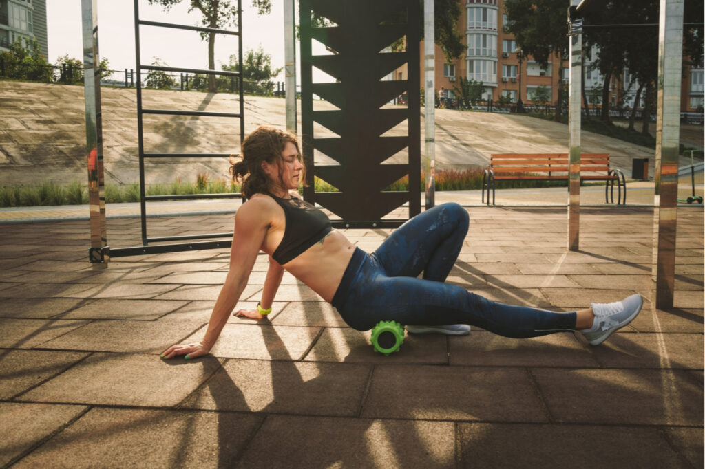 Woman athlete uses foam roller green for muscle recovery.