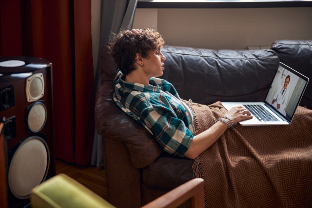 Attractive young man having online therapy with doctor at home.