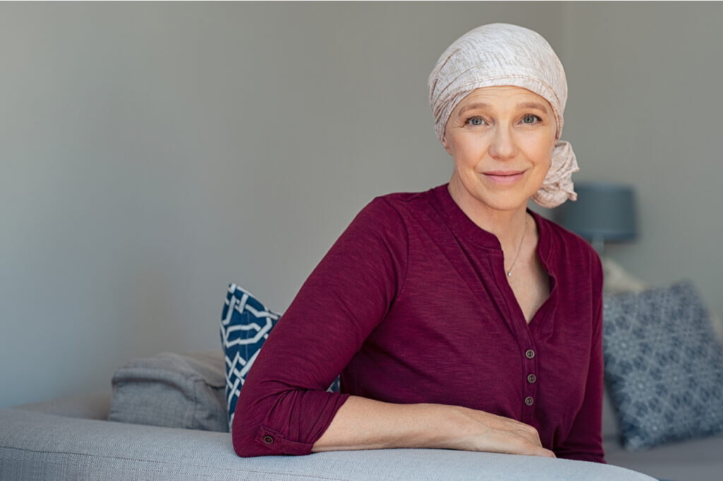 Woman with cancer in pink headscarf smiling sitting on couch at home.