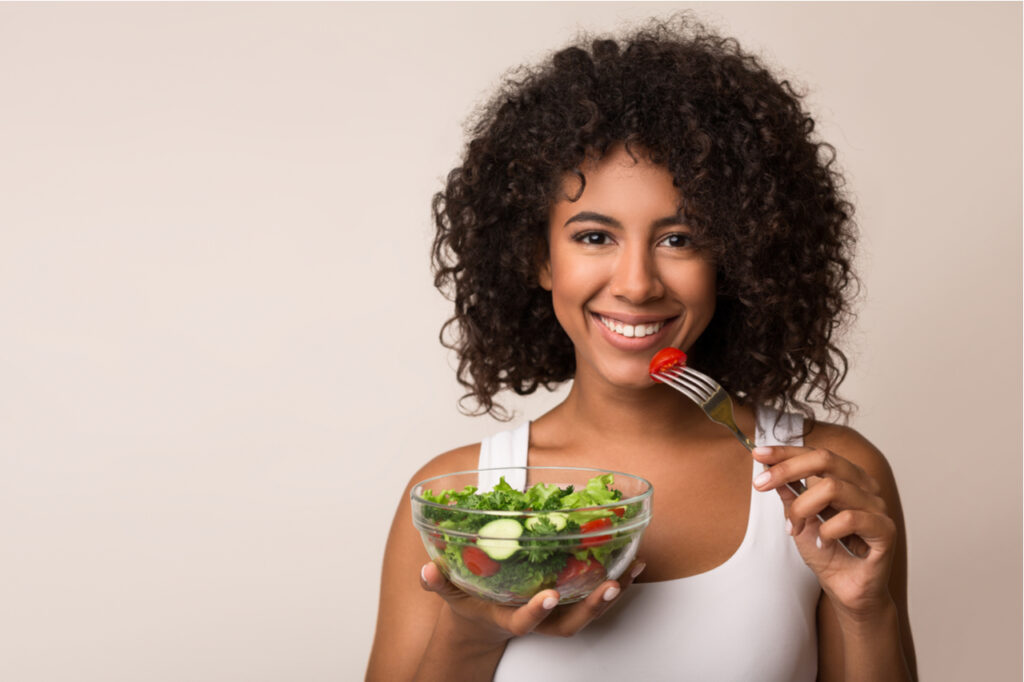 Woman eating vegetable salad over light background.