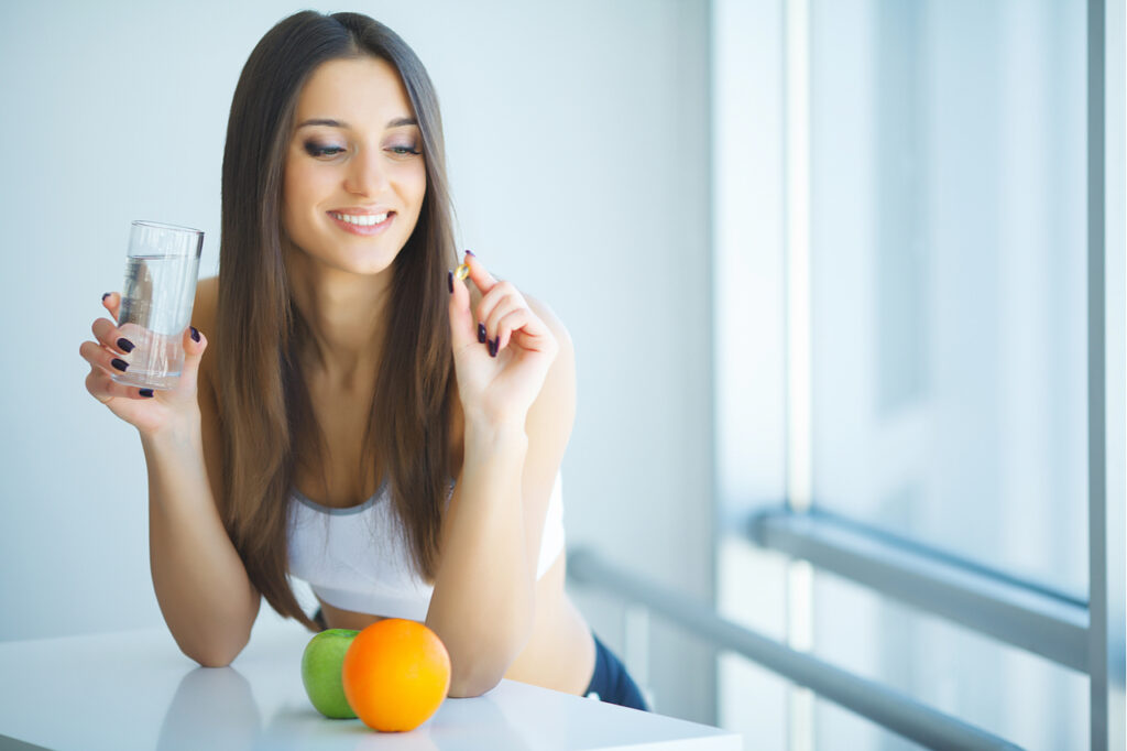 Woman taking vitamin arazo nutrition maximum strength l-carnitine.