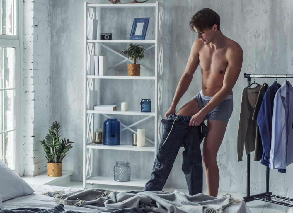 young man in boxer briefs is pulling on his pants while getting dressed at home