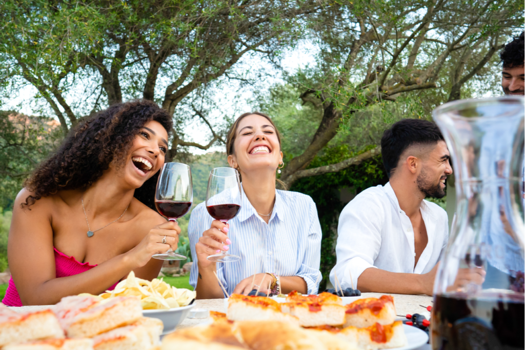 Mixed group of young happy friends celebrating outdoor with snacks and alcoholic drinks.