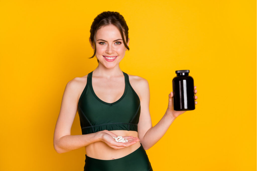 Woman taking supplement energy everyday regime isolated over bright yellow background