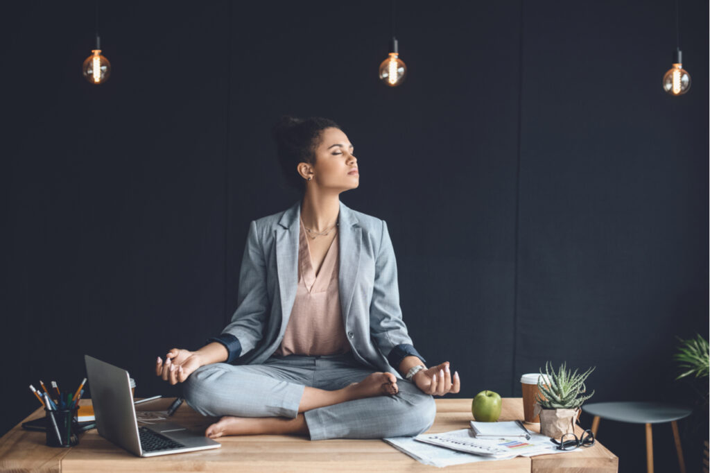Businesswoman sitting in lotus pose on table while meditating in office.